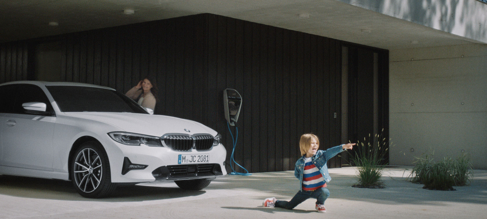 BMW plug-in hybrids boy in front of BMW hybrid vehicle at charging station
